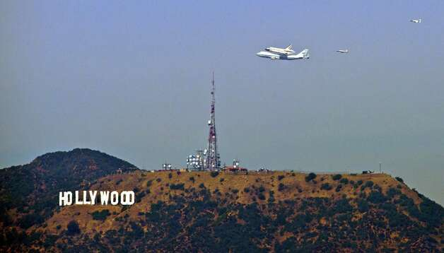 The Space Shuttle Endeavour atop a modified 747 passes the Hollywood Sign as seen from Dodger Stadium, Friday, Sept. 21, 2012, in Los Angeles, the last aerial hurrah before retiring to a Los Angeles museum. (AP Photo/Mark J. Terrill) Photo: Mark J. Terrill