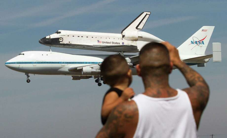 Spectators Mario Vasquez, 40, of Redondo Beach and his son Mario Jr., 2, watch as space shuttle Endeavour, atop NASA's Shuttle Carrier Aircraft, prepares to land at Los Angeles International Airport in Los Angeles, on Friday, Sept. 21, 2012.  (AP Photo/Ringo H.W. Chiu) Photo: Ringo H.W. Chiu