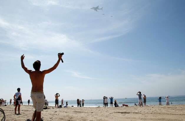 Spectators watch as the Space Shuttle Endeavour mounted on NASA's Shuttle Carrier Aircraft (SCA) flies near Santa Monica, Calif., Friday, Sept. 21, 2012. (AP Photo/Jae C. Hong) Photo: Jae C. Hong