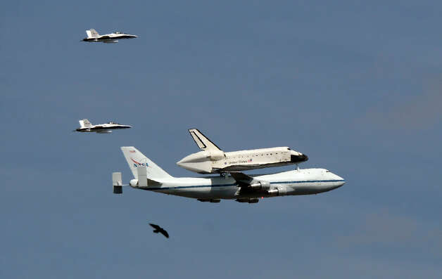The Space Shuttle Endeavour atop a modified 747 flies followed by two chase planes and a bird as near Dodger Stadium, Friday, Sept. 21, 2012, in Los Angeles, on a sightseeing tour of California, the last aerial hurrah before retiring to a Los Angeles museum. (AP Photo/Mark J. Terrill) Photo: Mark J. Terrill
