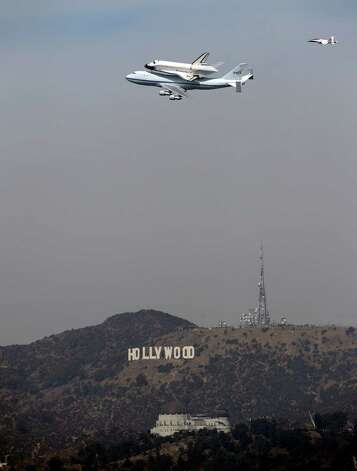 The Space Shuttle Endeavour atop a modified 747 passes the Hollywood Sign and the Griffith Observatory as seen from Dodger Stadium, Friday, Sept. 21, 2012, in Los Angeles. Endeavour will be permanently displayed at the California Science Center in Los Angeles.  (AP Photo/Mark J. Terrill) Photo: Mark J. Terrill