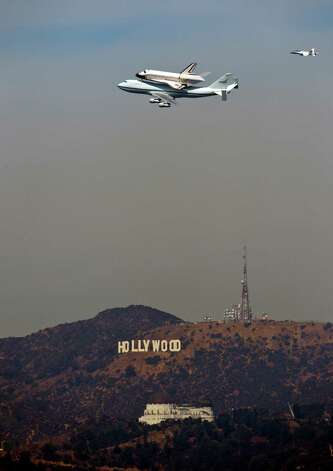 RETRANSMISSION FOR IMPROVED QUALITY--The Space Shuttle Endeavour atop a modified 747 passes the Hollywood Sign and the Griffith Observatory as seen from Dodger Stadium, Friday, Sept. 21, 2012, in Los Angeles, on a sightseeing tour of California, the last aerial hurrah before retiring to a Los Angeles museum. (AP Photo/Mark J. Terrill) Photo: Mark J. Terrill