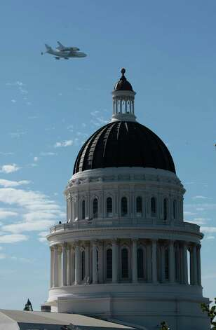 The space shuttle Endeavour passes over the California state Capitol, Friday, Sept. 21, 2012,  in Sacramento, Calif. Endeavour is making a final trek across the country to the California Science Center in Los Angeles, where it will be permanently displayed.(AP Photo/Rich Pedroncelli) Photo: Rich Pedroncelli
