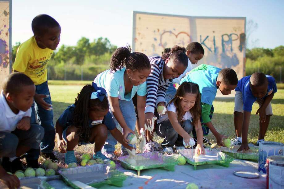 Students from Ms. Barnes first grade class, including Celeste Villatorro, center white, fight to get their tennis balls dipped in the paint. Photo: Todd Spoth / © TODD SPOTH, 2012