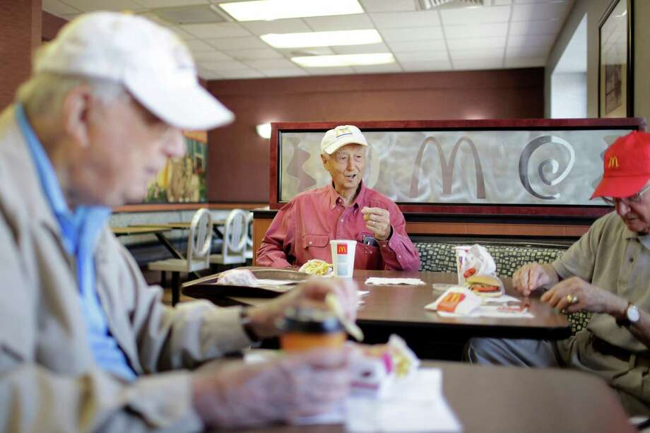 Willard Pennington, left, John Mawhinney and William Allison, right, swap stories while having lunch at the McDonald's on the corner of Briar Forest and Wilcrest. The friends, ranging in age from 89 to 99, have been meeting as a group for 15 years. Photo: TODD SPOTH / © TODD SPOTH, 2012