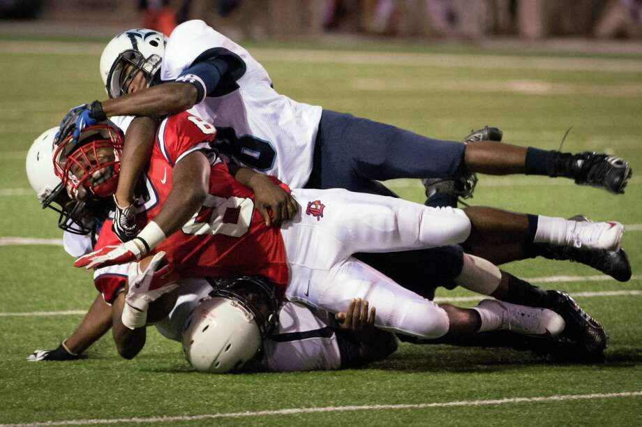 Lamar running back Darius Durall (8) is brought down by Elsik defensive lineman Jamarcus Turner (93), linebacker Charles Chendeka (36) and defensive back Lamar Richard (18) during the first quarter of a high school football game at Delmar Stadium, Friday, Sept. 21, 2012, in Houston. Photo: Smiley N. Pool, Houston Chronicle / © 2012  Houston Chronicle