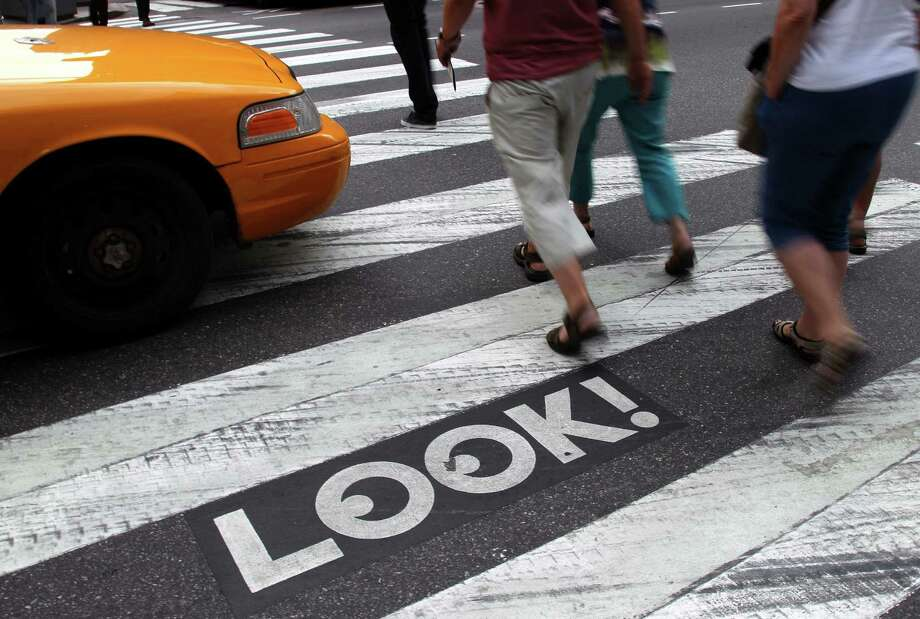 """Pedestrians walk past a """"Look!"""" sign on the crosswalk at the intersection of 42nd St. and 2nd Ave. in New York, Thursday, Sept. 20, 2012.  Crossing the street in New York City is complicated: Even when it's one-way, you should look both ways, and stop texting for a few seconds.  That's what city transportation officials tell pedestrians who often miss getting hit in the chaotic every-which-way-including-loose mill of vehicles, bicycles, scooters and sometimes, carriage horses.  They're making their point visible with """"LOOK!"""" signs stenciled at 110 of the most dangerous intersections in the city's five boroughs.  (AP Photo/Seth Wenig) Photo: Seth Wenig"""