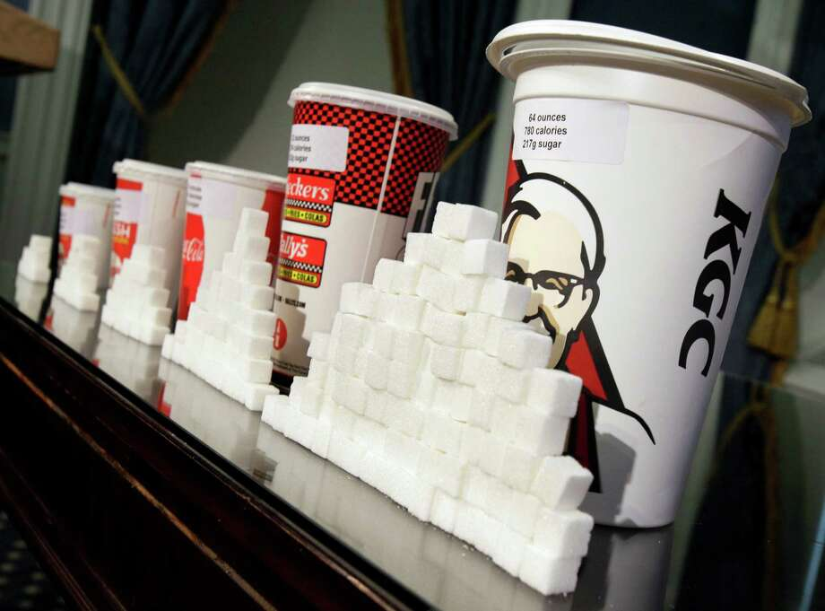 FILE - This Thursday, May 31, 2012 file photo shows a display of various size soft drink cups next to stacks of sugar cubes at a news conference at New York's City Hall. New research greatly strengthens the case against soda and other sugary drinks as culprits in the obesity epidemic. Two major experiments found that children and teens gained less weight when they regularly drank calorie-free beverages instead of sugary ones. A third study gives the first clear evidence that consuming sugary drinks interacts with genes that affect weight. Scientists say the results add weight to the push for taxes, size limits and other policies to curb consumption. (AP Photo/Richard Drew, File) Photo: Richard Drew