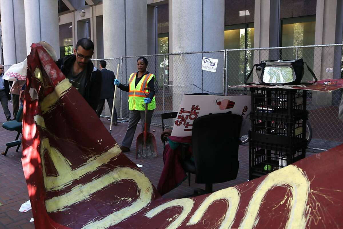 Occupy protesters removing their belongings in front of the Federal Reserve building in San Francisco, Calif., as the department of public works cleans their area on Tuesday, September 18, 2012.