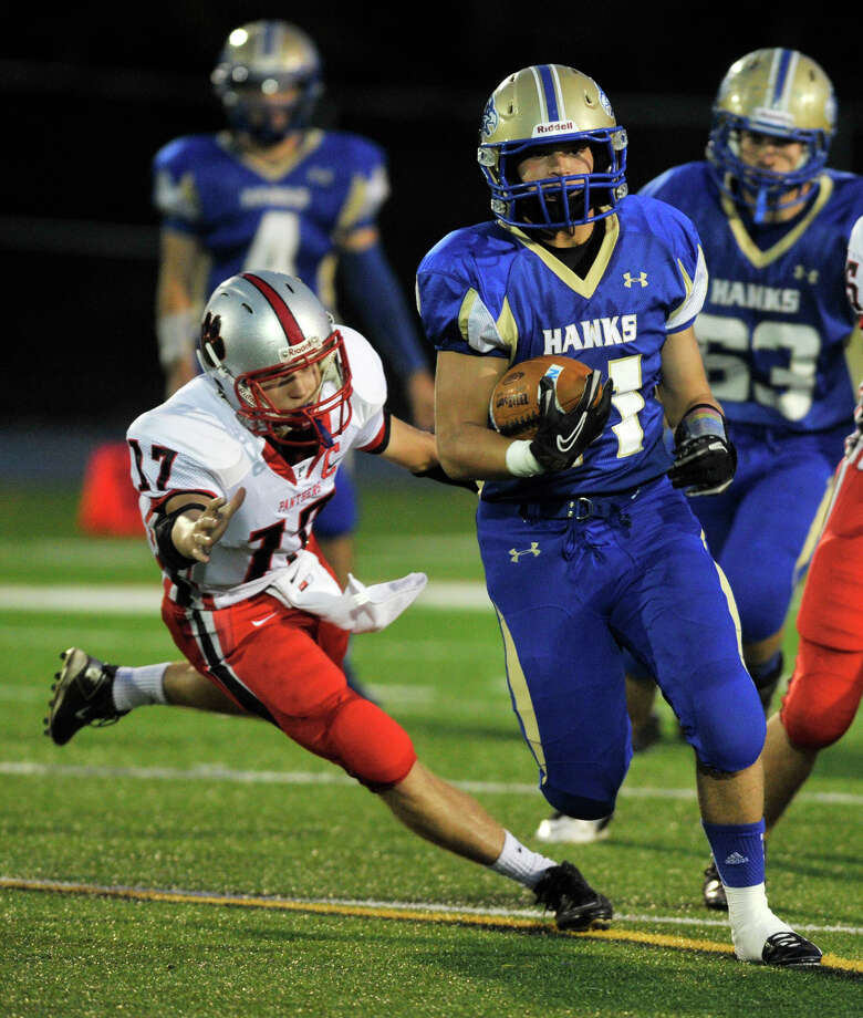 Newtown's Cooper Gold runs the ball while being tailed by Pomperaug's Carl Gatzendorfer during their game at Newtown High School on Friday, Sept. 21, 2012. Newtown won, 42-7. Photo: Jason Rearick / The News-Times
