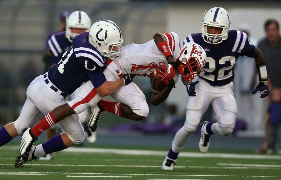 Crosby wide receiver Raelon Singleton (15) is tackled by Dayton's Kevin Barton during the first half of a high school football game, Friday, September 21, 2012 at Bronco Stadium in Dayton, TX. Photo: Eric Christian Smith, For The Chronicle