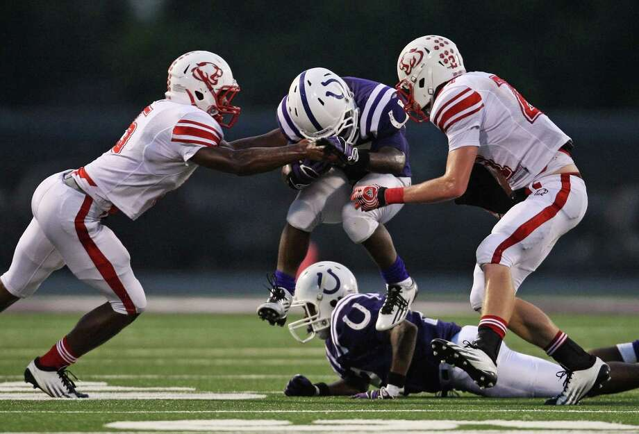 Dayton running back Kyle McBride (18) is tackled by Crosby's Eric Owens (left) and Kyle Williams during the first half of a high school football game, Friday, September 21, 2012 at Bronco Stadium in Dayton, TX. Photo: Eric Christian Smith, For The Chronicle