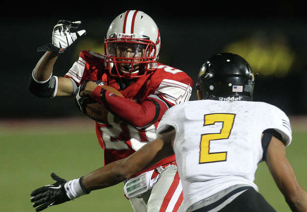 Judson's Brandon Sanders (20) attempts to run around East Central's Austin Jupe (02) during their game at D.W. Rutledge Stadium on Friday, Sept. 21, 2012. Photo: Kin Man Hui, Express-News / ©2012 San Antonio Express-News