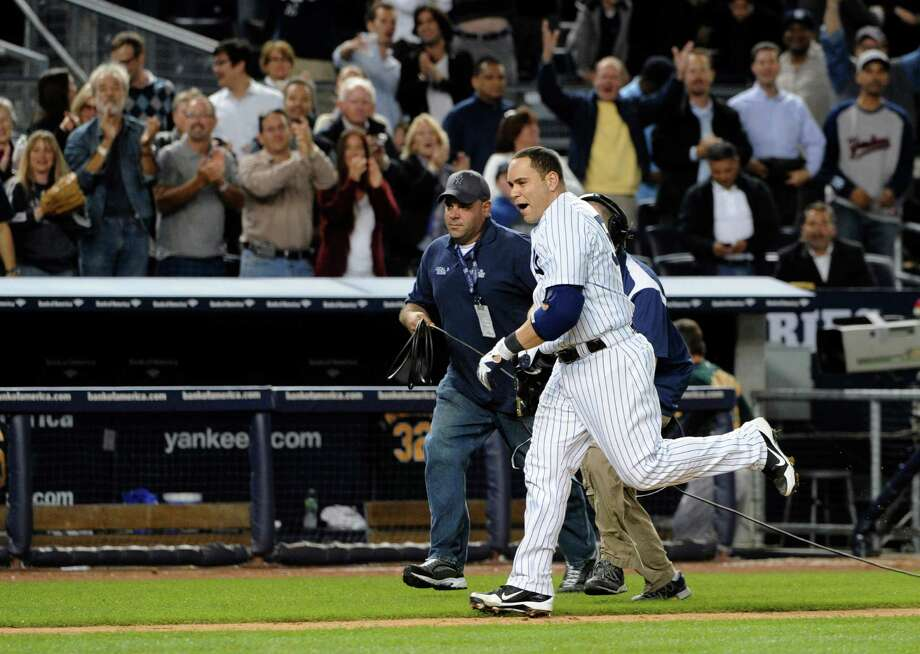 Fans cheer as New York Yankees' Russell Martin runs down the third base line headed to home plate after hitting a solo home run off Oakland Athletics relief pitcher Sean Doolittle to give the Yankees a 2-1 win, in the 10th inning of a baseball game Friday, Sept. 21, 2012, at Yankee Stadium in New York. (AP Photo/Kathy Kmonicek) Photo: Kathy Kmonicek