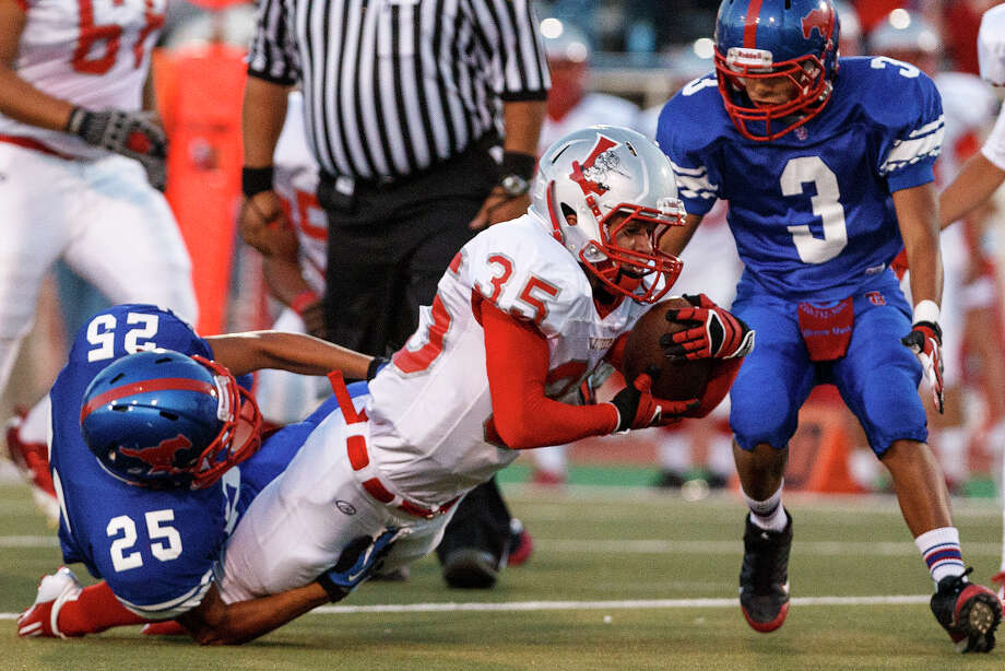 Lee running back Josh Caulk stretches for extra yardage after being tackled by Jefferson's Justin Lujan during their game at Alamo Stadium  on Sept. 21, 2012. Caulk ran for 162 yards on 28 carries and scored a touchdown to help Lee take a 49-35 victory over the Mustangs.  MARVIN PFEIFFER/ mpfeiffer@express-news.net Photo: MARVIN PFEIFFER, Express-News / Express-News 2012