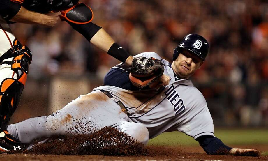 San Francisco Giants catcher Buster Posey tags out San Diego Padres Chase Headley at home plate in the sixth inning of their MLB baseball game Friday September 21, 2012. In San Francisco California. Photo: Lance Iversen, The Chronicle