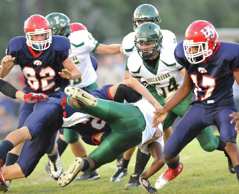 Buccaneer #14, Adam Trent, takes a very hard hit as he is brought down by Hawk #12, Andrew Martel.  Trent left the game in an ambulance with his arms taped. The East Chambers Buccaneers football team played the Hardin-Jefferson Hawks at 7:00 p.m. Friday night at Hawk Stadium.  At the half, the Hawks were ahead 6-0.  Dave Ryan/The Enterprise Photo: Dave Ryan