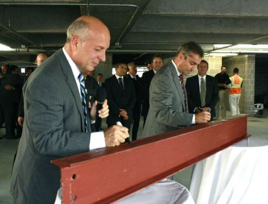 Top BBVA executives Manolo Sánchez, left, and Ángel Cano autograph a ceremonial beam during the topping-out event at the tower.