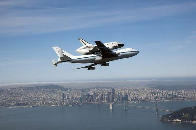 In this photo provided by NASA, space shuttle Endeavour and its modified 747 carrier aircraft soar over the Bay Bridge that connects San Francisco to Oakland during the final portion of its tour of California, Friday, Sept. 21, 2012. (AP Photo/NASA, Carla Thomas) Photo: Carla Thomas, Associated Press