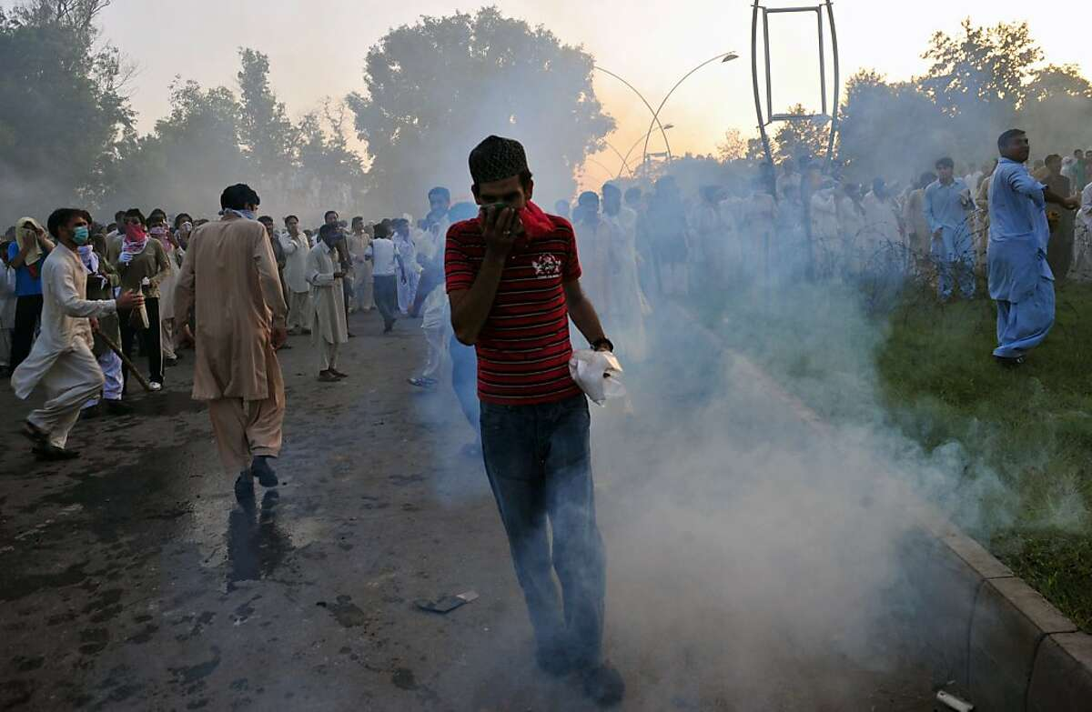A Pakistani Muslim demonstrator reacts after police fire teargas shells during a protest near the US consulate in Islamabad on September 21, 2012. At least 13 people died and nearly 200 were wounded in Pakistan during violent protests on Friday condemning a US-made film insulting Islam, defying a government call for only peaceful demonstrations, officials said. AFP PHOTO/Farooq NAEEMFAROOQ NAEEM/AFP/GettyImages