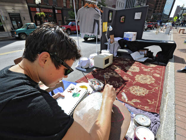 Ashley Blovin of Albany paints on North Pearl street on PARK(ing) Day Friday, Sept. 21, 2012 in Albany, N.Y. PARK(ing) Day is an annual open-source global event where citizens, artists and activists collaborate to temporarily transform metered parking spaces into ?PARK(ing)? spaces. (Lori Van Buren / Times Union) Photo: Lori Van Buren