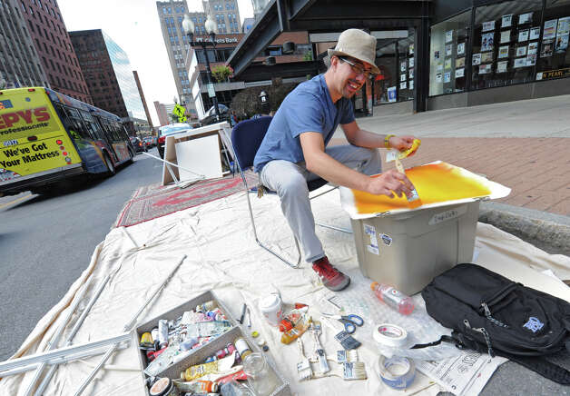 Tony Iadicicco of Albany paints an abstract piece of art on North Pearl street on PARK(ing) Day Friday, Sept. 21, 2012 in Albany, N.Y. PARK(ing) Day is an annual open-source global event where citizens, artists and activists collaborate to temporarily transform metered parking spaces into ?PARK(ing)? spaces. (Lori Van Buren / Times Union) Photo: Lori Van Buren