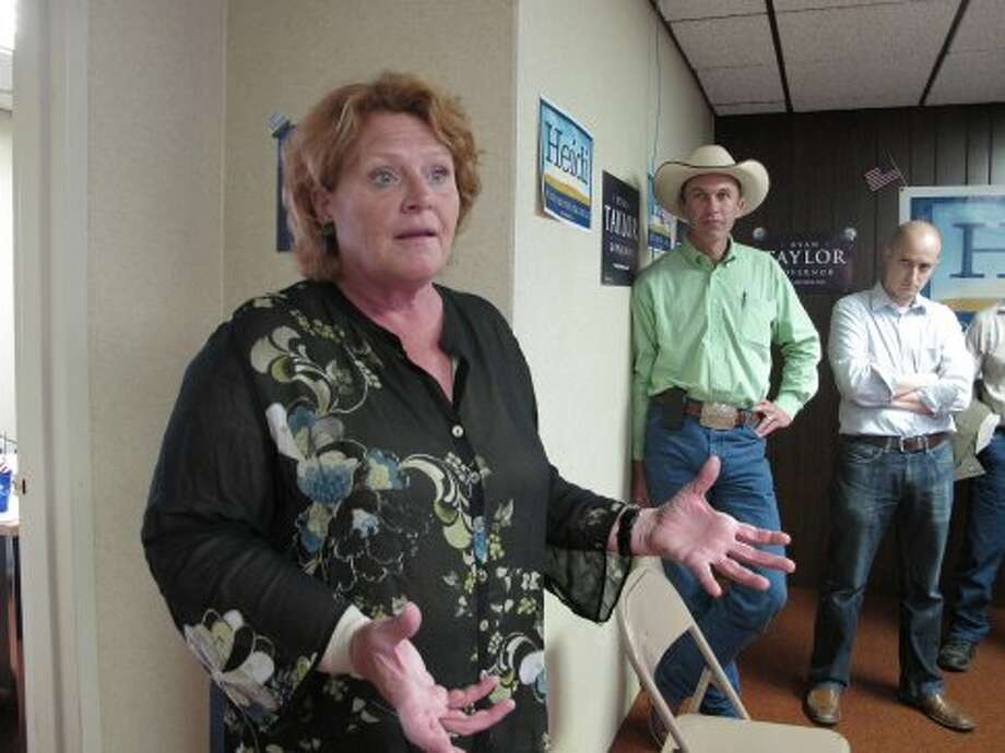 In this photo taken Saturday, Aug. 11, 2012, Heidi Heitkamp, left, the North Dakota Democratic candidate for the U.S. Senate, speaks during the opening of a North Dakota Democratic campaign office in Dickinson, N.D. At right is Ryan Taylor, with hat, the North Dakota Democratic candidate for governor, and Ryan Nagle, a Democratic campaign staffer. Heitkamp is locked in a tight race with Republican Rick Berg to succeed retiring Democratic U.S. Sen. Kent Conrad, and the race's outcome is considered crucial to GOP chances of winning Senate control. (Dale Wetzel / Associated Press)