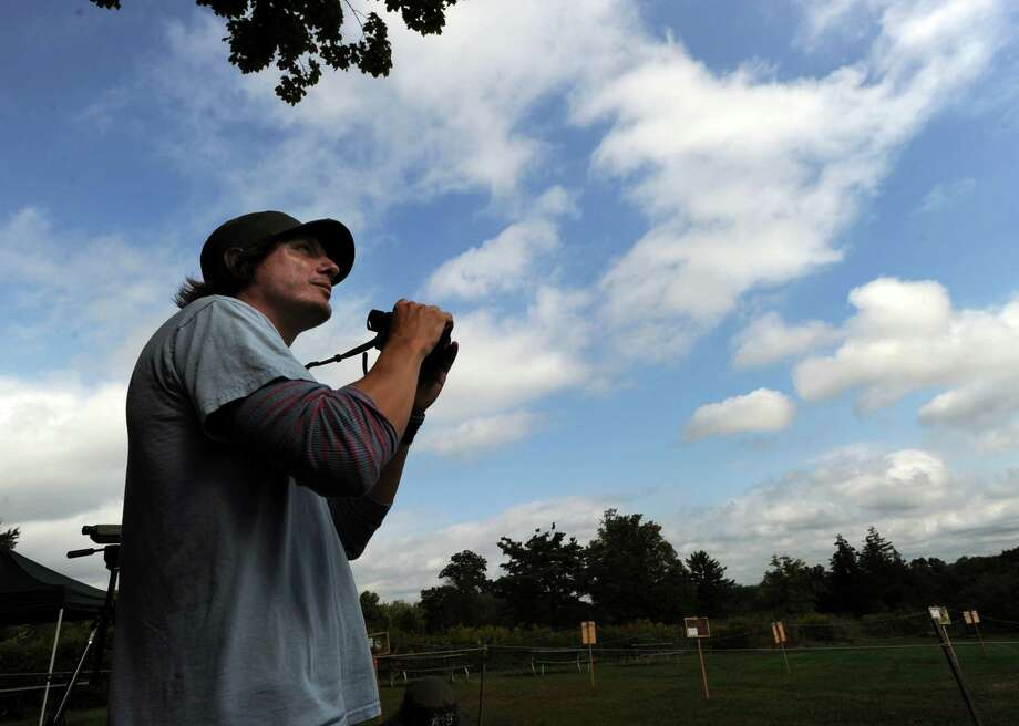 Hawk Expert Luke Tiller of Audubon Greenwich scans the sky holding binoculars while counting hawks during the 14th annual HawkWatch Festival & Green Bazaar at Audubon Greenwich, Saturday, Sept. 22, 2012. Tiller said that as of Aug. 20, the offical hawk count has reached 16,652, the second best count since 1995. Photo: Bob Luckey / Greenwich Time