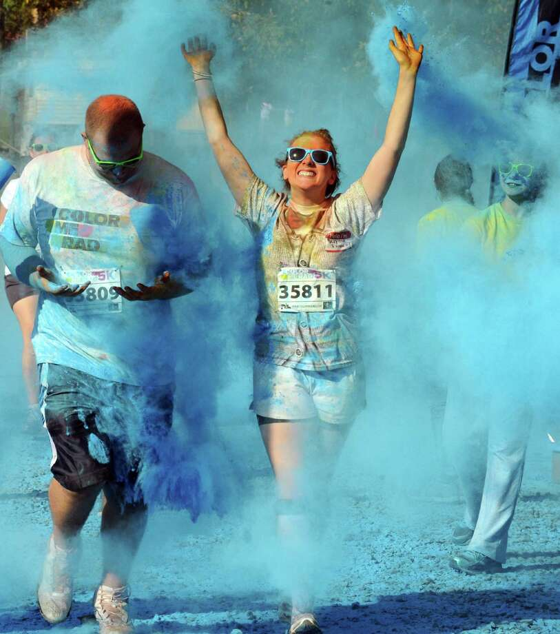 Elizabeth Buehler, right and Jordan Brand emerge from a cloud of blue during the Color Me Rad Albany run at the fairgrounds in Altamont, NY Saturday Sept. 22, 2012. (Michael P. Farrell/Times Union) Photo: Michael P. Farrell
