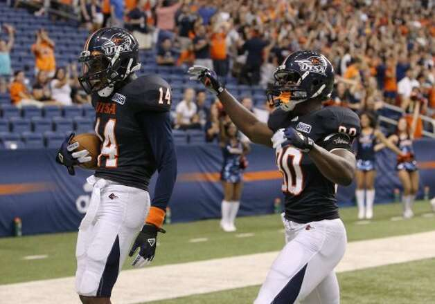 UTSA's Tristan Wade (14) reacts after intercepting a pass for a touchdown against Northwestern Oklahoma State as teammate Cole Hicks (80) goes to congratulate Wade at the Alamodome on Saturday, Sept. 22, 2012. (Kin Man Hui / SAN ANTONIO EXPRESS-NEWS)