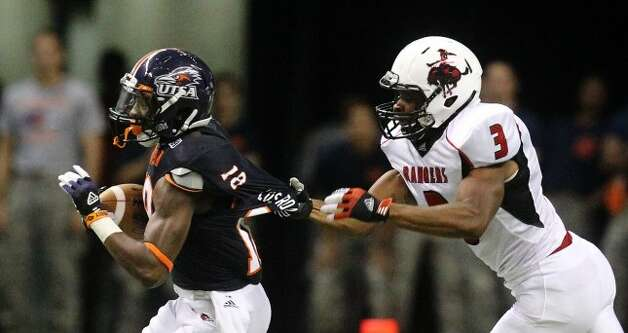 UTSA's Kenny Harrison (18) gets his jersey pulled by Northwestern Oklahoma State's Marvin Desir (03) during a punt return in the first half at the Alamodome on Saturday, Sept. 22, 2012. (Kin Man Hui / SAN ANTONIO EXPRESS-NEWS)