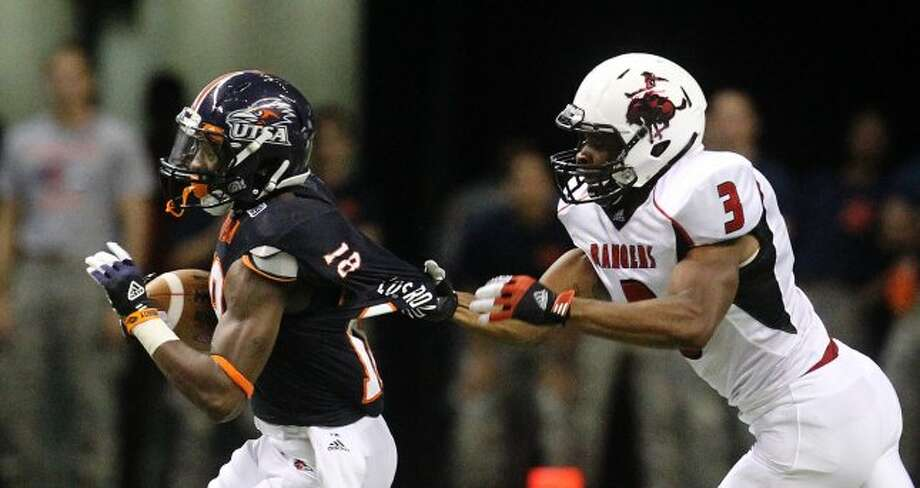 UTSA's Kenny Harrison (18) gets his jersey pulled by Northwestern Oklahoma State's Marvin Desir (3) during a punt return in the first half at the Alamodome on Saturday, Sept. 22, 2012. (Kin Man Hui / SAN ANTONIO EXPRESS-NEWS)