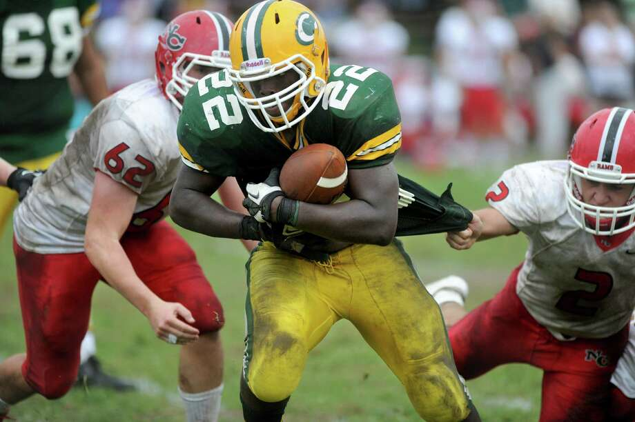 Trinity Catholic's Shaquan Howsie carries the ball as New Canaan's Cole Harris grabs him by the jersey during Saturday's game at Trinity Catholic High School on September 22, 2012. Photo: Lindsay Niegelberg / Stamford Advocate