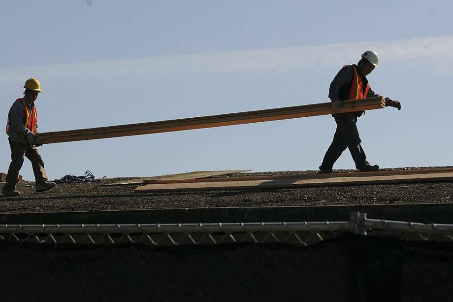 Workers install a new roof on the crumbling Lake Merced boathouse. It is part of the second phase of improvements. Photo: Erik Verduzco, Special To The Chronicle