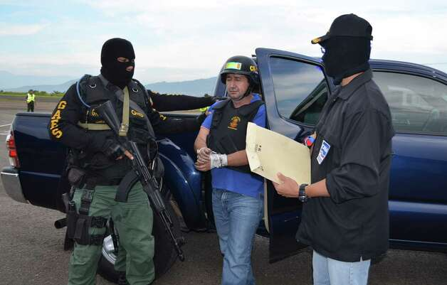 The arrest of alleged Colombian drug trafficker Daniel Barrera (center), also known as El Loco, was the result of a complex endeavor involving Colombia, Venezuela, Britain and the United States. Photo: Associated Press / Ministry of Popular Power for In