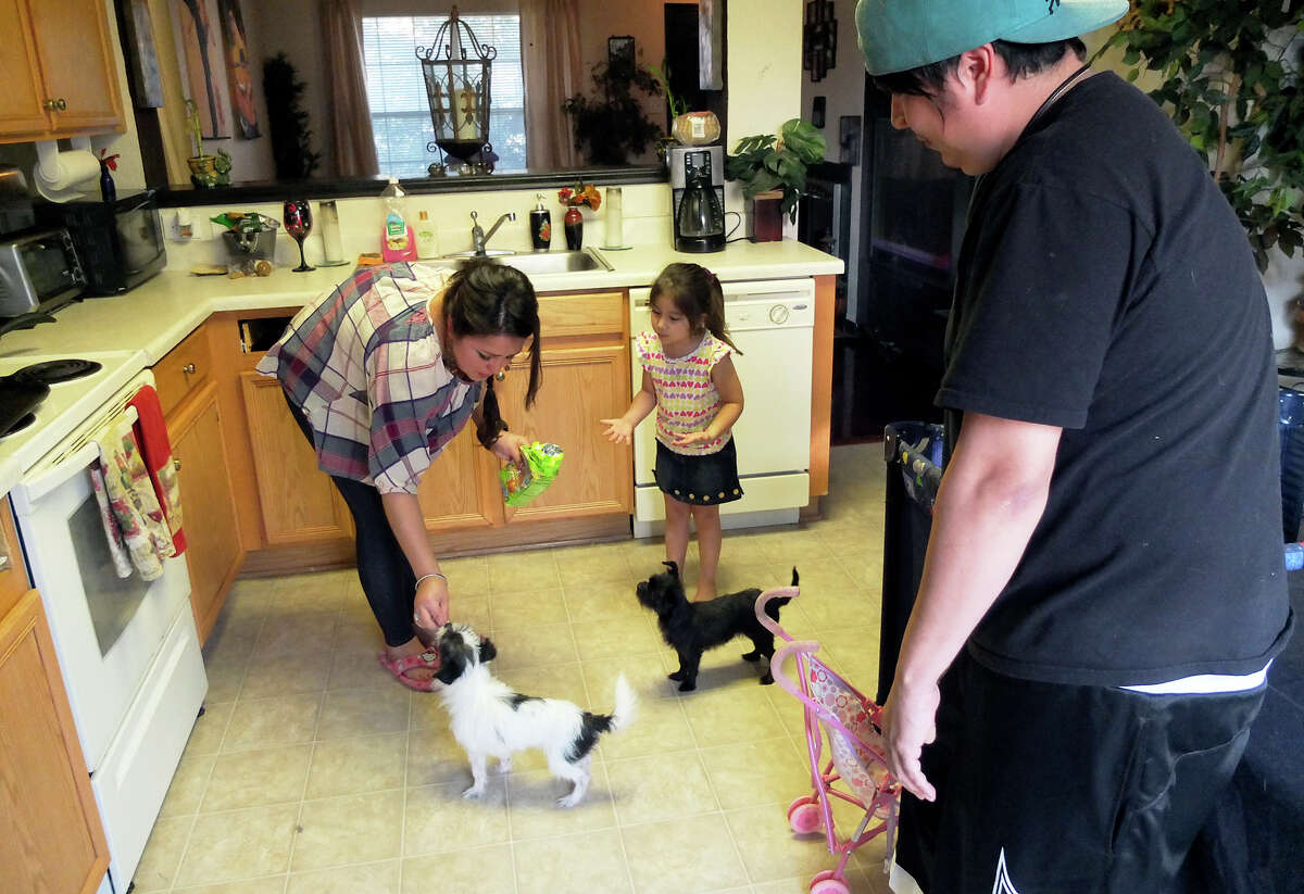 Angelica Rodriguez (left) feeds snacks to her pet dogs while daughter Katia Ramirez and boyfriend Carlos Ramirez look on. Rodriguez is looking for apartments to rent once the sale of her home is completed.