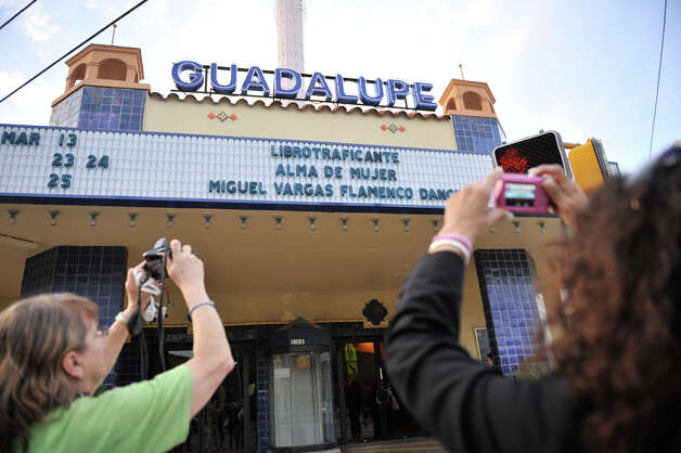 Gloria Rubac (left) and Susie Moreno photograph the outside of the Guadalupe Theater as they arrived for the Librotraficane Banned Book Bash on March 13, 2012. Photo: Robin Jerstad, For The Express-News / SAN ANTONIO EXPRESS-NEWS