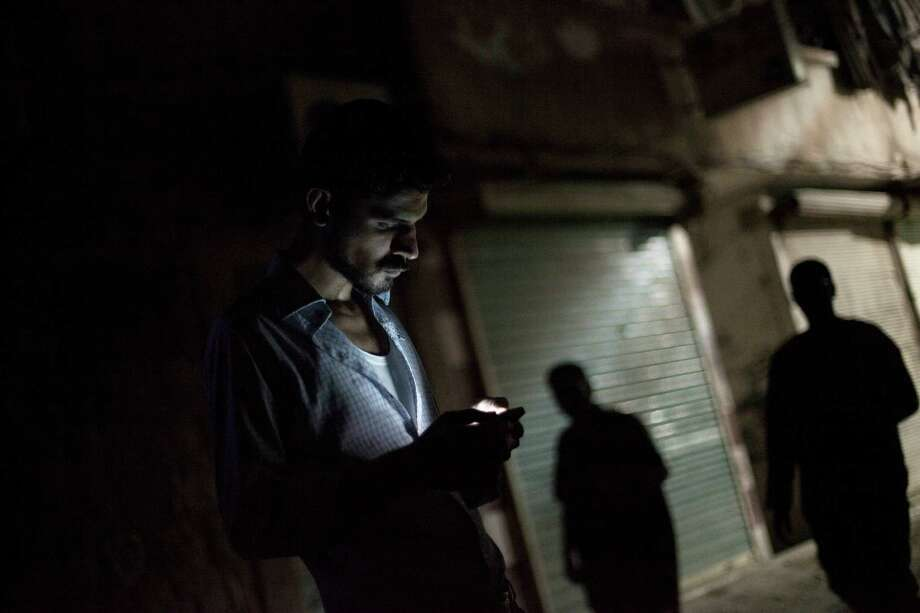 In this Friday, Sept. 21, 2012 photo, a Syrian man looks at his mobile phone in the Bustan al-Qasr neighborhood of Aleppo, Syria. The Britain-based Syrian Observatory for Human Rights said Friday that nearly 30,000 Syrians have been killed during the 18-month uprising against the Assad regime. (AP Photo/ Manu Brabo) Photo: Manu Brabo