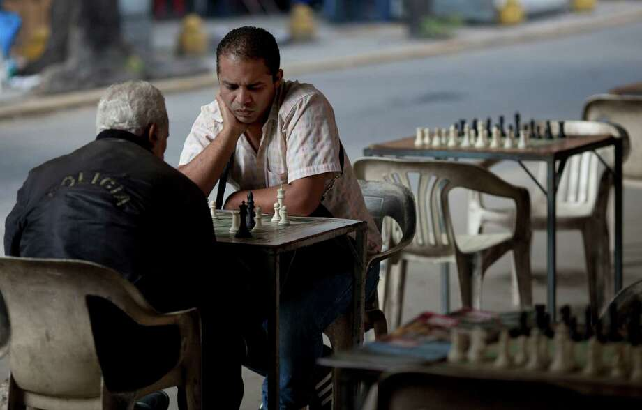 In this Sept. 4, 2012 photo, two men play chess on a street in Caracas, Venezuela. Nearly 14 years after President Hugo Chavez took office, and despite the biggest oil bonanza in Venezuela's history, there's little outward sign of the nearly one trillion petrodollars that have flowed into the country. The populist president has used the oil wealth to buttress his support through cash handouts, state-run grocery stores and a gamut of other social programs. With more money in the economy, incomes are higher and the number of people living in poverty has fallen. Yet some experts say Chavez could have done much more to improve the country's infrastructure, boost its economy and invest in the very oil industry that keeps Venezuela afloat. (AP Photo/Ariana Cubillos) Photo: Ariana Cubillos
