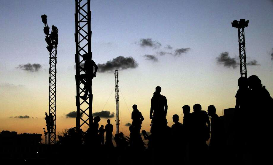 Libyans climb up electricity towers to watch the march against Ansar al-Shariah Brigades and other Islamic militias, in Benghazi, Libya, Friday, Sept. 21, 2012. The recent attack that killed the U.S. ambassador and three other Americans has sparked a backlash among frustrated Libyans against the heavily armed gunmen, including Islamic extremists, who run rampant in their cities. More than 10,000 people poured into a main boulevard of Benghazi, demanding that militias disband as the public tries to do what Libya's weak central government has been unable to.(AP Photo/Mohammad Hannon) Photo: Mohammad Hannon