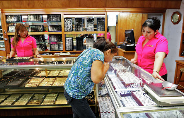 Local customer Maria Luisa Moreno, center, looks over jewelry at the Gold Coin, Inc. on Convent Avenue in downtown Laredo, Wednesday, Sept. 19, 2012. Helping her out is Lupita Paredes, right. Cleaning jewelry is Denise Ventura, left. Downtown businesses have suffered with sales due to various factors including the drug war across the Rio Grande in Nuevo Laredo and difficulties in crossing the U.S. Customs checkpoints according to storeowners. Photo: Jerry Lara, San Antonio Express-News / © 2012 San Antonio Express-News