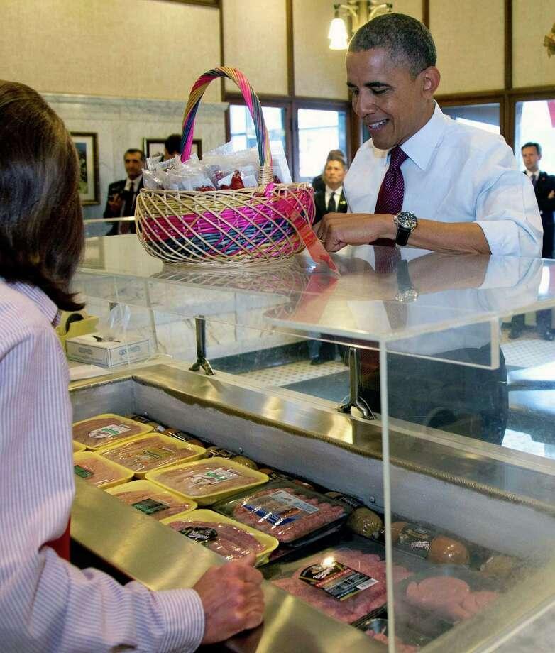 President Barack Obama picks out sausages at Usinger's Sausage, Saturday, Sept. 22, 2012, in Milwaukee. (AP Photo/Carolyn Kaster) Photo: Carolyn Kaster