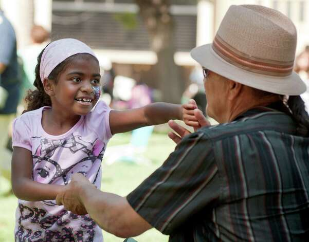 Renee Sanchez, 7, dances with her father, Max Martinez, at Jazz'SAlive. The jazz festival in Travis Park ends at 11 tonight. Photo: Darren Abate, For The Express-News