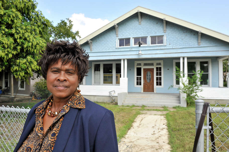 Dee Smith stands in front of her Dignowity Hill bungalow. She bought the home at auction for $3,200 and has invested $80,000 in renovations in the structure. Photo: Robin Jerstad, For The Express-News