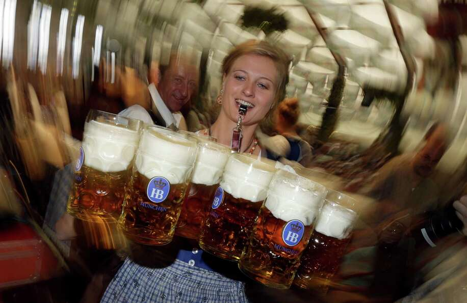 A waitress carries beer mugs in the Hofbraeuhaus tent after the opening of the famous Bavarian
