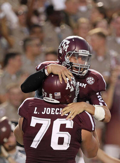 Texas A&M University quarterback Johnny Manziel (2) jumps into offensive linesman Luke Joeckel's (76