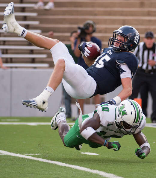 Rice wide receiver Jordan Taylor (15) is upended by Marshall safety Okechukwu Okoroha (10) during th