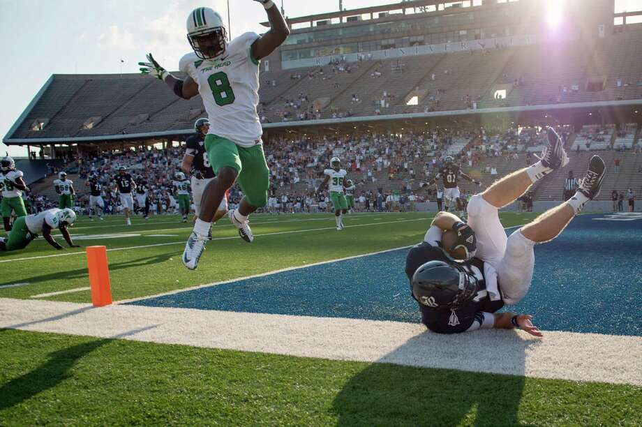 Rice quarterback Taylor McHargue (16) dives into the end zone past Marshall defensive back Keith Baxter (8) at the end of a 43-yard touchdown run during the fourth quarter of a college football game at Rice Stadium, Saturday, Sept. 22, 2012, in Houston. Photo: Smiley N. Pool, Houston Chronicle / © 2012  Houston Chronicle