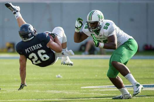 Rice running back Turner Petersen (26) is sent flying as Marshall defensive lineman Jeremiah Taylor (58) closes in during the fourth quarter of a college football game at Rice Stadium, Saturday, Sept. 22, 2012, in Houston. Photo: Smiley N. Pool, Houston Chronicle / © 2012  Houston Chronicle