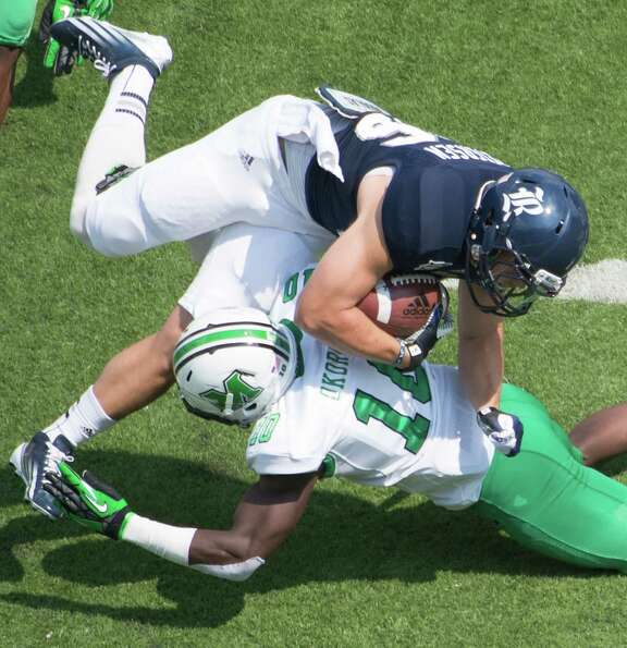 Rice running back Turner Petersen (26) is upended by Marshall safety Okechukwu Okoroha (10) during t